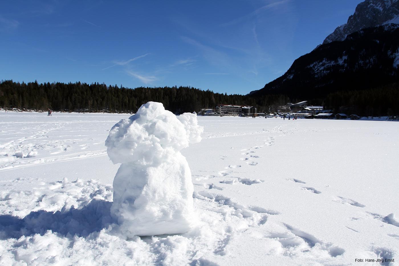 MANN IN WEISS Da wo sonst das Wasser grünlich schimmert, steht ein Schneemann und blickt hinüber zum Eibsee-Hotel.