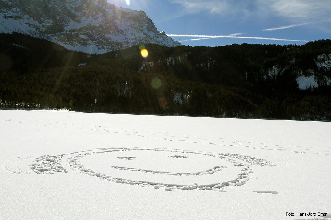 EIN SMILEY FÜR DEN EIBSEE In diesem Winter war der See am Fuß der Zugspitze komplett zugefroren. Klein im Bild ist am Zugspitzmassiv die Panoramagondel zu erkennen, die von Ehrwald (Österreich) aus auf den Zugspitzgipfel fährt.