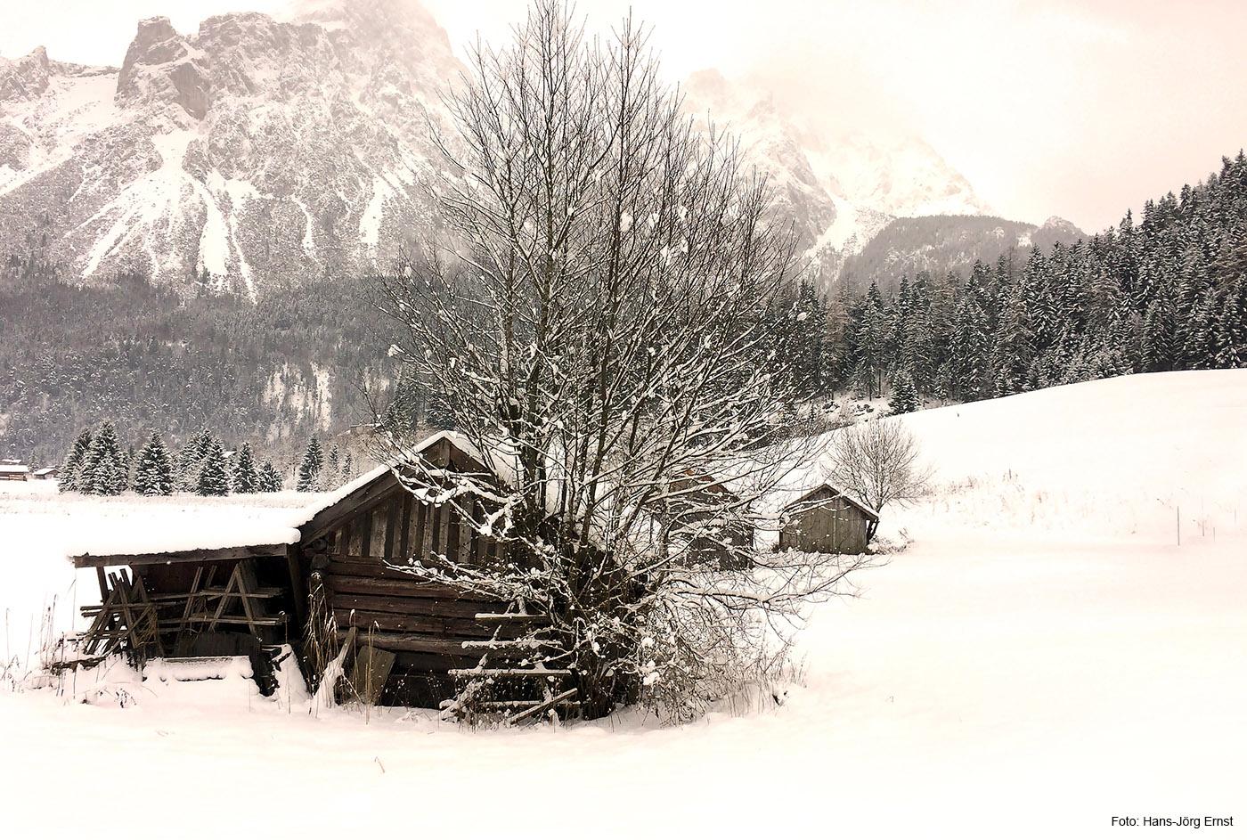 ZUGSPITZ-ARENA Schön sind die vielen Hütten und Heuschober auf den Wiesen zwischen Lermoos und Ehrwald. Dahinter ragen die Berge in den Himmel.